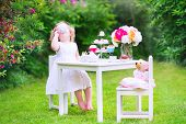 picture of birthday  - Adorable funny toddler girl with curly hair wearing a colorful dress on her birthday playing tea party with a teddy bear doll toy dishes cup cakes and muffins in a sunny summer garden - JPG
