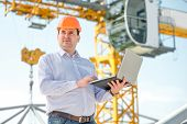 stock photo of supervision  - A foreman with laptop at the construction supervising the project - JPG