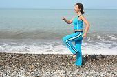 woman wearing sporty clothers is making exercise on sea coast