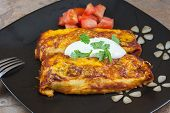 pic of enchiladas  - Homemade beef bean and cheese enchiladas with tomatoes and sour cream - JPG