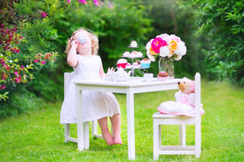 pic of baby doll  - Adorable funny toddler girl with curly hair wearing a colorful dress on her birthday playing tea party with a teddy bear doll toy dishes cup cakes and muffins in a sunny summer garden - JPG