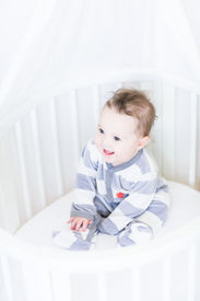 foto of bassinet  - Sweet Baby Girl Sitting In A Round White Bassinet - JPG