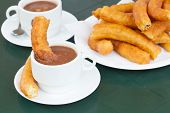stock photo of churros  - traditional spanish pastry - two cups of chocolate with churros