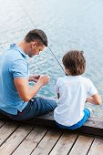 picture of fishing rod  - Rear view of father and son sitting at the quayside and preparing fishing rod for fishing - JPG