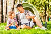 stock photo of tent  - Cheerful father and son sitting near the tent and drinking hot tea from metal cups while camping in the forest together - JPG