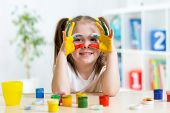 foto of cheers  - cute cheerful kid girl showing her hands painted in bright colors - JPG