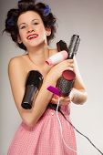 stock photo of hair curlers  - Young woman preparing for date having fun with curlers styling hair with many accessories comb brush hairdreyer on gray - JPG