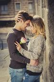 stock photo of candid  - candid portrait of beautiful European couple with rose in love kissing on street alley celebrating Valentines day with passion against stone wall on urban background - JPG