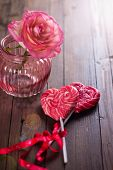 stock photo of lollipops  - Lollipop hearts and beautiful flower rose on dark wooden background. Selective focus is on lollipop.