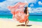 stock photo of woman  - Young pregnant woman with pink cloth fluttering in the wind on a tropical beach - JPG