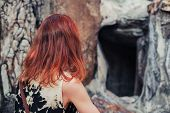 stock photo of cave woman  - A young woman is looking at the entrance to a small cave - JPG