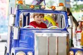 foto of funfair  - Funny little kid boy riding on a merry - JPG