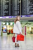 foto of board-walk  - Young woman at international airport checking electronic board and waiting for her flight - JPG