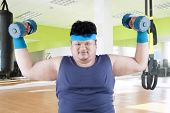 image of obese man  - Fat man exercise in fitness center by lifting two dumbbells - JPG