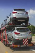 stock photo of car carrier  - delivery of brandnew cars transportation on the highway - JPG