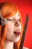 stock photo of licking  - Young beauty redhead woman licking katana sword - JPG