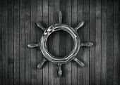 pic of ship steering wheel  - Decorative steering wheel on a wooden background - JPG