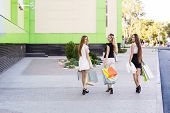 pic of girl walking away  - Girls holding shopping bags and walk around the shops - JPG