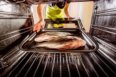 image of oven  - Housewife prepares dorado fish in the oven - JPG