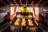 stock photo of oven  - Baking Gingerbread man in the oven - JPG