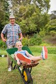 foto of wheelbarrow  - Happy grandfather and his granddaughter with a wheelbarrow in a sunny day - JPG