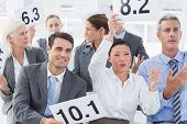 image of interview  - Smiling interview panel holding score cards in bright office - JPG