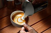 image of latte  - Making of cafe latte art on the wooded table - JPG