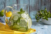 stock photo of pitcher  - Fruit water with lemon, lime, cucumber and mint in glass pitcher