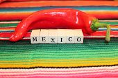 picture of mexican fiesta  - Traditional Mexican fiesta poncho rug in bright colors with sombrero background with copy space - JPG