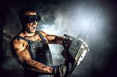 foto of man chainsaw  - Shouting muscular man with a chainsaw over dark grunge background - JPG