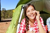 pic of suntanning  - Camping woman applying sunscreen sun cream sunblock suntan lotion in tent smiling happy outdoors in forest - JPG