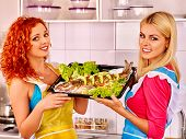 stock photo of oven  - Happy women prepare grilled fish in oven - JPG