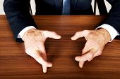 stock photo of fingers crossed  - Close up of businessman cross fingers on the desk - JPG