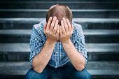 stock photo of sad  - Outdoor portrait of sad young man covering his face with hands sitting on stairs - JPG