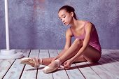 image of ballet shoes  - young ballerina putting on her ballet shoes on the wooden floor on a pink background - JPG