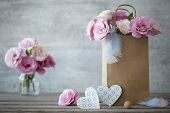 stock photo of blue rose  - Still life romantic background with pink roses and blue hearts - JPG