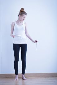 image of anorexic  - Very slim anorexic woman measuring her waist - JPG