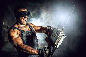 stock photo of man chainsaw  - Shouting muscular man with a chainsaw over dark grunge background - JPG