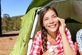 stock photo of sun tan lotion  - Camping woman applying sunscreen sun cream sunblock suntan lotion in tent smiling happy outdoors in forest - JPG