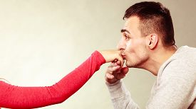 stock photo of politeness  - Polite man husband kissing woman hand palm - JPG