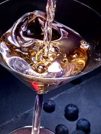 stock photo of cocktail menu  - Blueberry gold drink with pouring cocktail on black background - JPG