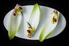 foto of endive  - Fancy Waldorf salad on endive leaves served in elegant setting - JPG
