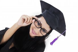 picture of graduation gown  - High angle view of female graduate student smiling at the camera while wearing graduation gown - JPG