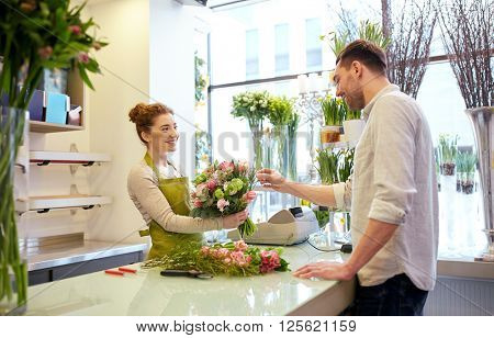 people, shopping, sale, floristry and consumerism concept - happy smiling florist woman making bouqu