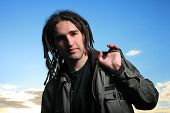 foto of rastaman  - Young man with dreadlocks over blue sky - JPG