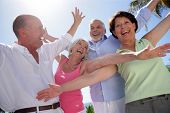 picture of 55-60 years old  - Portrait of senior couples smiling with arms up - JPG