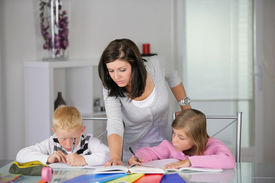 stock photo of mother child  - Portrait of young woman helping a boy and a girl in doing homework - JPG