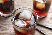Glass of refreshing cola with ice on wooden table, closeup poster