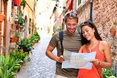 Europe travel tourists couple looking at map to find directions walking in old streets of spanish ci poster