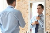 Young businessman looking at himself in mirror indoors poster
